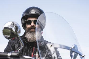 Portrait of bearded biker wearing helmet and sunglasses sitting on his motorcycle - JASF000399