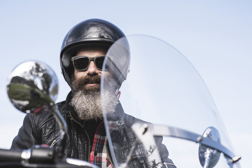 Portrait of bearded biker wearing helmet and sunglasses sitting on his motorcycle - JASF000399