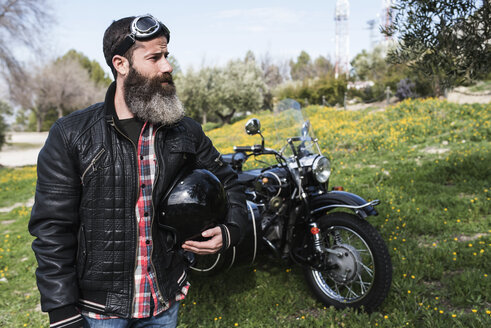 Biker standing on a meadow in front of his motorcycle - JASF000402