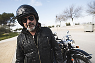 Portrait of smoking biker wearing helmet and sunglasses standing on a road in front of his motorcycle - JASF000405