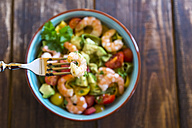 Noodle salad with avocado, tomato and shrimps in bowl on wood, fork with shrimp - SARF002547