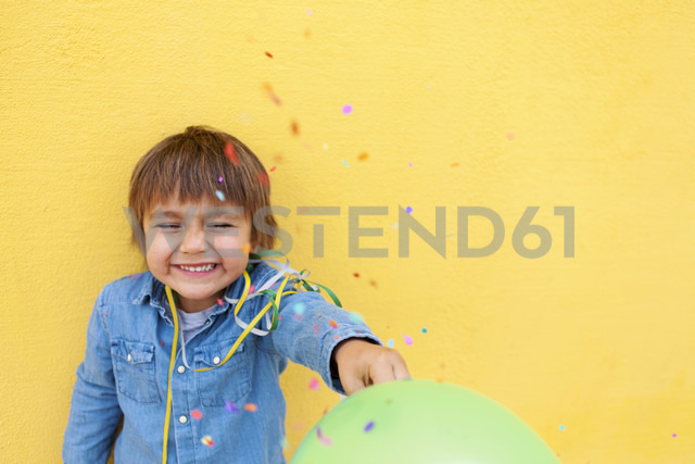 Smiling little boy with green balloon, streamer standing in front of yellow wall while confetti falling down - VABF000145