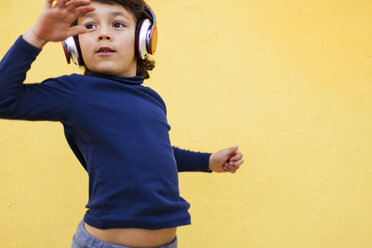 Dancing little boy in front of yellow wall hearing music with headphones - VABF000148