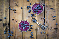 Two glasses of chia blueberry pudding and two tea spoons on wood - LVF004517