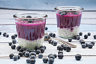 Two glasses of chia blueberry pudding, blueberries and two tea spoons on wood - LVF004520