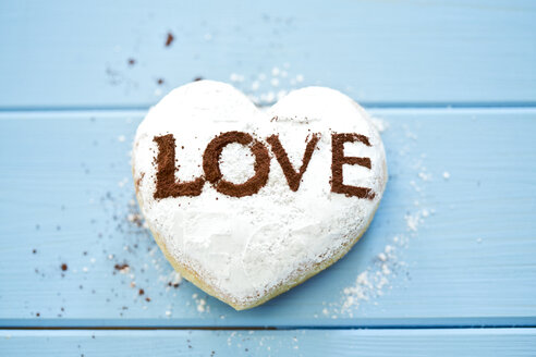 Pastry with the word 'Love' on light blue wood - MAEF011290