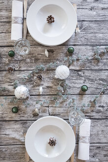 Two place settings on laid table at Christmas time - LVF004527