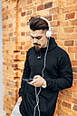 Portrait of young man leaning against brick wall listening music with headphones - MGOF001430