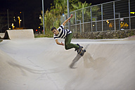 Spain, Barcelona, young man skateboarding in a skatepark by night - SKCF000053