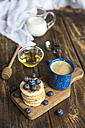Stack of mini pancakes, blueberries, bowl of honey, milk and a cup of coffee - SARF002549