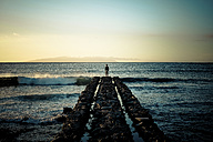 Spain, Canary Islands, Tenerife, back view of child standing at pier looking at the sea - SIP000175