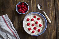 Yogurt with raspberries in bowl on wood - SARF002556