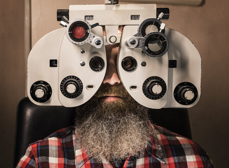 Bearded man making an eye test - JASF000409