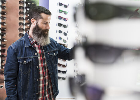 Bearded man in optical store chosing glasses - JASF000412