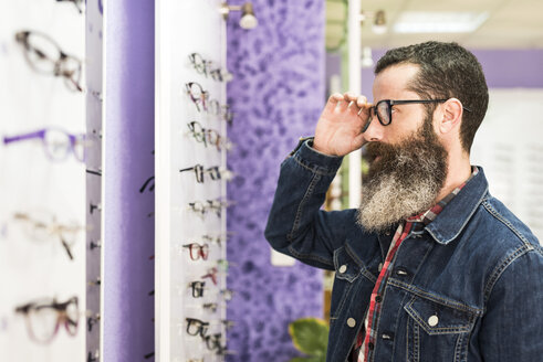 Bearded man in optical store trying on glasses and looking in mirror - JASF000415