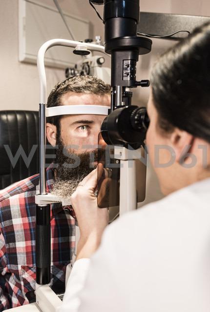 Optometrist examining eyes of a bearded man - JASF000424