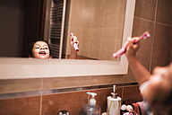 Mirror image of little girl standing in the bathroom going to brush her teeth - JASF000433