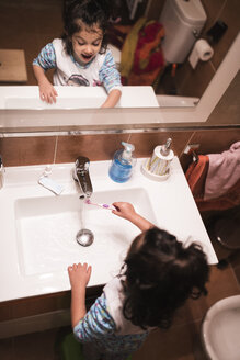 Mirror image of little girl standing in the bathroom going to brush her teeth - JASF000436