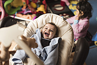 Happy baby boy lying in baby carrier while his little sister playing in the background - JASF000439