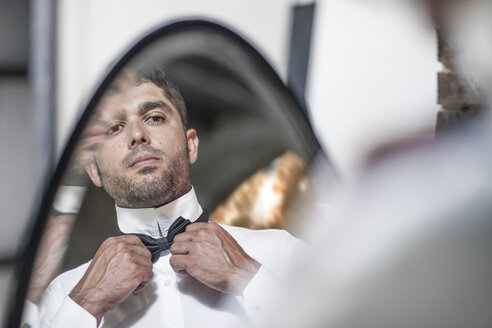 Man looking in mirror adjusting bowtie - ZEF008444