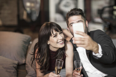 Smiling couple in elegant clothing drinking champagne in bed and taking a selfie - ZEF008462