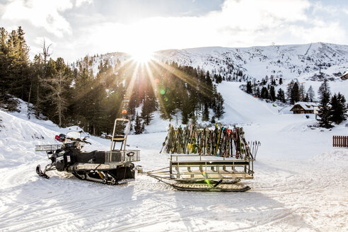 Austria, Turracher Hoehe, snowmobile and skis in winter landscape - DAW000519