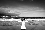 Spain, Tenerife, woman with closed eyes standing on the beach at seafront - SIPF000181