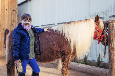 Portrait of smiling girl grooming pony - XCF000060
