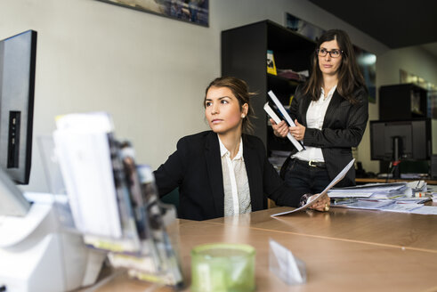 Two women in office looking at computer monitor - JASF000441