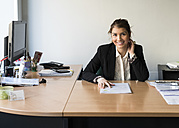 Portrait of smiling young woman at office desk - JASF000444
