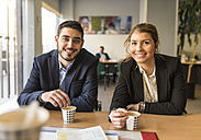 Portrait of smiling man and woman sitting at office desk with coffee - JASF000474