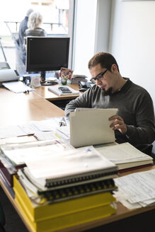 Man doing paperwork at desk in office - JASF000486