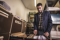 Man searching for files at basement - JASF000489