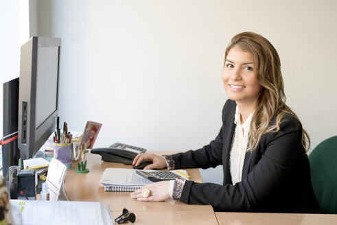 Portrait of smiling young woman at office desk - JASF000498