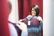 Smiling woman in fitting room looking in mirror - JASF000505