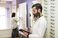 Bearded optometrist in his store looking at organizer - JASF000520