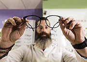 Bearded optometrist in his store looking at glasses - JASF000523
