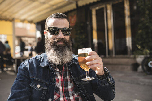 Portrait of bearded man wearing sunglasses drinking beer at outdoor gastronomy - JASF000529