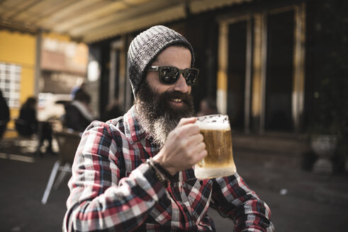 Portrait of hipster wearing sunglasses and woolly hat drinking beer at outdoor gastronomy - JASF000532