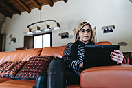 Woman sitting on the couch in the living room of her farmhouse using digital tablet - JRFF000432