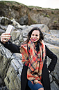 Spain, Ferrol, portrait of smiling  woman taking a selfie with her smartphone in front of rocks - RAEF000878