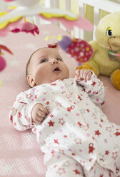 Baby girl lying in a baby cot looking at mobile - DEGF000637