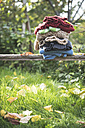 Stack of warm clothing in a garden - DEGF000643