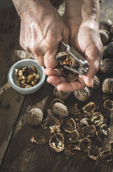 Woman's hands cracking walnuts with nutcracker - DEGF000646
