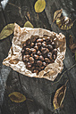Roasted sweet chestnuts on brown paper and autumn leaves on wood - DEGF000652