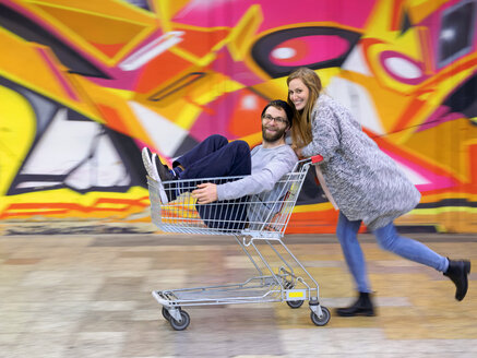 Young woman pushing man in shopping cart, laughing and running - LAF001608