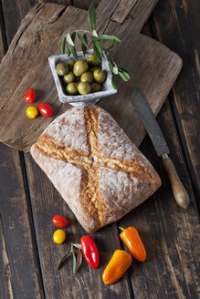 Ciabatta bread with green olives in bowl, tomatoes and mini capsicum on wood - CSF027161