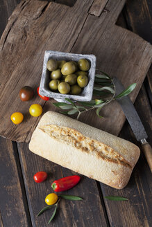 Ciabatta bread with green olives in bowl, tomatoes and mini capsicum on wood - CSF027164