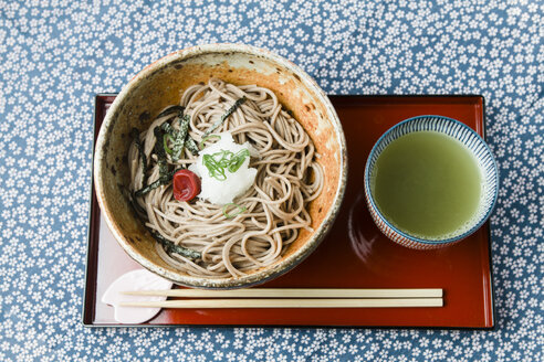 Bowl of Soba noodles on red lacquer plate and bowl of green tea - FLF001307