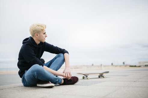 Spain, Torredembarra, young skateboarder sitting on the ground relaxing - JRFF000438
